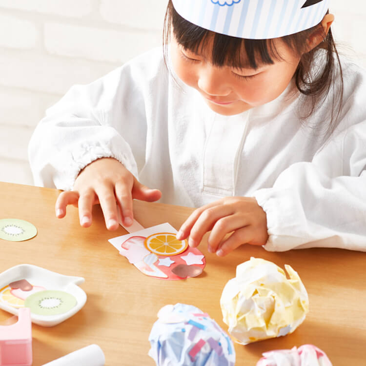 ペーパークラフトでアイスクリーム屋さんの工作をしている女の子
