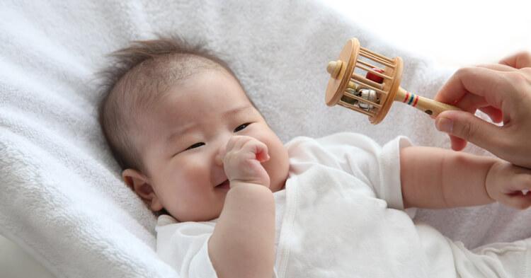 赤ちゃんのおもちゃ_ガラガラで遊ぶ乳児