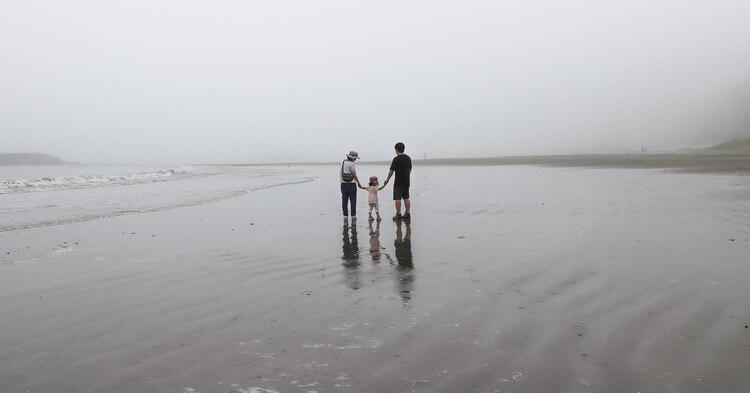 年賀状写真 海辺で手をつなぐ家族の後ろ姿
