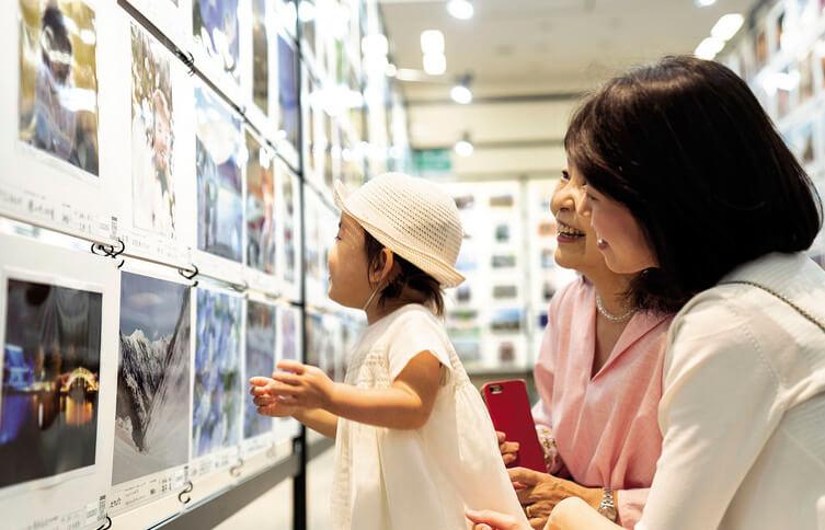 あなたが主役の写真展2021 写真を見る親子連れ 赤ちゃんと母親